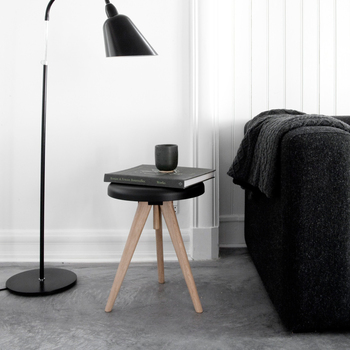 モノトーンなスツールをさりげなくソファ横に。ブラックのソファやライトとのコーディネートがスタイリッシュで、本を置いておくだけでもサマになります。