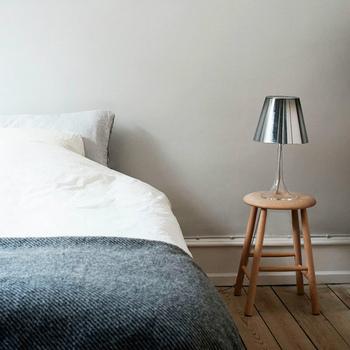 ノルディックスツールをライトを置く台としてベッドサイドに。手の届くところにライトを置けば、ベッドに横になりながら本を読めますね。