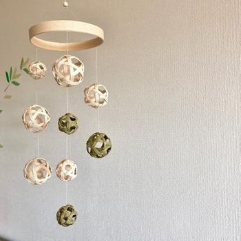 天井から吊るして空間を彩るモービル。クラフトバンドで作ったボールをランダムに吊るしています。オリーブ×オフホワイトのナチュラルカラーがお部屋に癒しを運んでくれそうです。