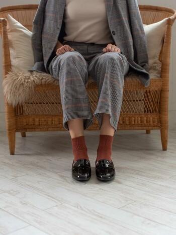 セットアップを着こなす時、裾からちらりと覗く靴下は大事なお洒落ポイントです。ここではお洋服のチェックに使われている暖色カラーを靴下で取り入れ、アクセントにしながらも統一感を狙っています。