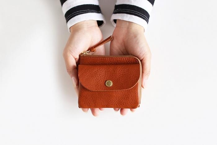 両手に収まるころんとしたサイズ感とフォルムが可愛いお財布。薄いのでミニバッグの中にもするんと入ります。正面のボタンがキュートです。