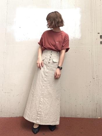 リネンのナチュラルな質感がキュートなロングスカート。テラコッタ×ベージュで秋らしい配色のコーデに。足元や腕時計に黒を使って、全体の印象を引き締めています。