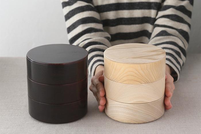コロンとかわいい丸型の重箱。漆仕上げのダークな「漆」と、木目が際立つウレタン仕上げの「白木」の2種類。
