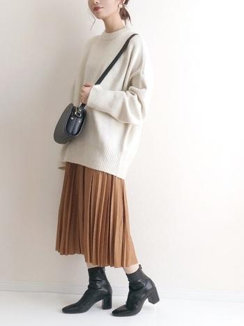 ゆるっと大きめの白ニットとプリーツスカートの組み合わせ。滑らかに揺れるひだが上品な印象です。ショートブーツやミニショルダーなど黒小物で、全体を程よく引き締めています。