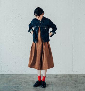 ブラウンの秋色ワンピースにインディゴデニムジャケットを合わせて、ほどよくカジュアルに仕上げて。赤の靴下がシンプルなコーデのワンポイントになった遊び心のあるコーデです。