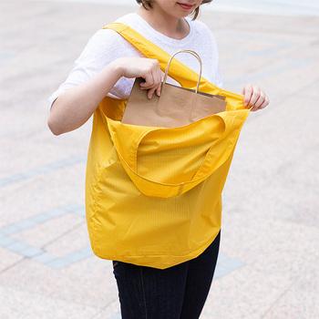 手で持ったり肩にかけたりどちらでも使いやすいサイズとフォルム。しかも袋口が大きく開く作りなので、肩にかけたままでお財布やメモ帳、スマホなどの荷物の出し入れがスムーズに行えるのも使用していて助かります。