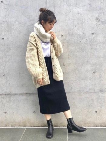 ベーシックカラーのひざ下丈スカートに、黒のブーツを合わせたシックな着こなしです。白のロゴTとスヌードは色味を統一して、ベージュのニットカーディガンで柔らかな印象にまとめています。