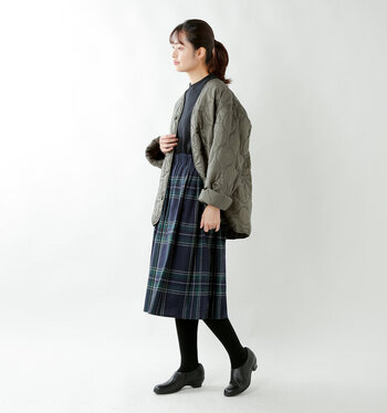 シンプルな黒トップスをタックインして、タイツやシューズも黒でまとめたシック×カジュアルなコーディネートに。スカートと色味を合わせたカーキのダウンジャケットを合わせて、冬でも暖かく過ごせるスタイリングに仕上げています。