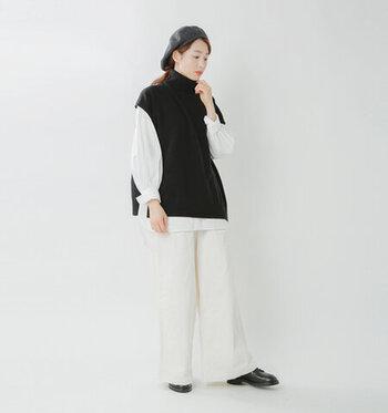 タートルネックデザインのニットベストに、白のブラウスを重ねたコーディネートです。ボトムスも白のワイドパンツで色を揃えて、シンプルだけどおしゃれなモノトーンスタイルに。シューズやベレー帽も黒系で揃えているので、ボリューム感のあるトップスもスッキリ見えが叶います。