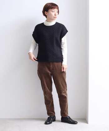 黒のアラン編みニットベストに、白のタートルネックトップスを重ねた着こなし。ブラウンのコーデュロイパンツを合わせて、ちょっぴりメンズライクなコーディネートにまとめています。足元も黒のかっちりシューズで、クールな印象に。