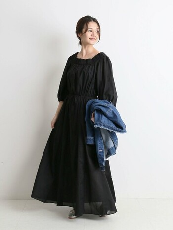 マキシ丈のブラックワンピース。フレアなスカート部だけでなく、全体も空気を含んだようなシルエットで着心地も良さそう。コーデが重たい印象になるかもと心配な方は、羽織りにデニムジャケットを合わせてみて。