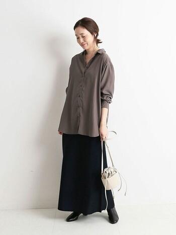 艶感が素敵なシャツは、上までボタンを留めずにラフに着こなしましょう。ブラックのスカートとブーツで足長効果も期待できます。ポイント作りはコロンとしたバッグで解決。