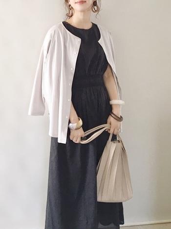 黒いカラーのワンピースに、淡いカラーをプラスしてやさしい印象のコーデに。バッグにトレンドのプリーツデザインを選ぶことで、一気に旬の装いに仕上がります。存在感のあるバングルを肌なじみの良いブラウン系でまとめて、簡単におしゃれに。