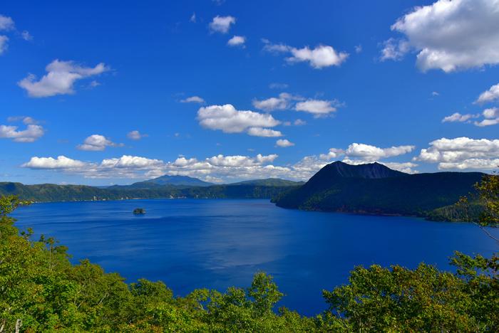 摩周湖は日本では一番の、世界ではロシアのバイカル湖に次いで二番目の透明度を誇る美しい湖です。『霧の摩周湖』と異名を持ち、立ち込める霧に包まれているイメージが強い摩周湖ですが、よく晴れた日には、真っ青な湖面を見ることができ、その美しさから湖面の色は『摩周ブルー』と形容されています。