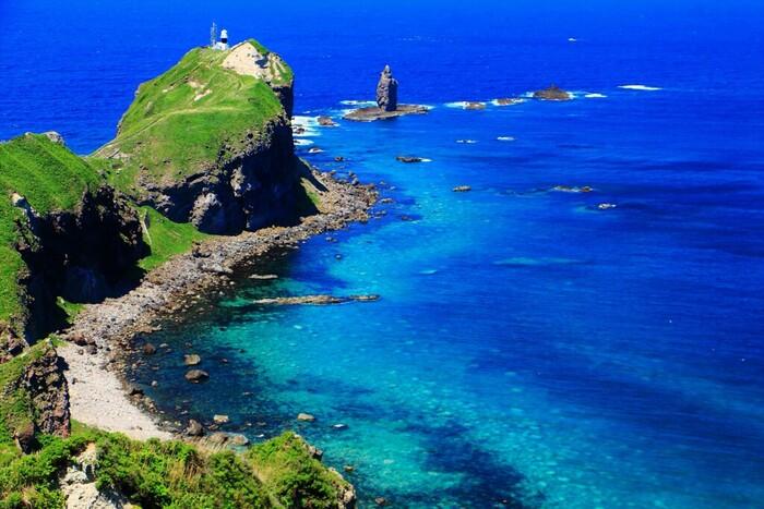 切り立った断崖から眺める日本海の青い色は『シャコタンブルー』と呼ばれており、その透明度は海底まで見えるほど澄み渡っています。神威岬の先端部は岩山が海へそのまま落ち込む断崖絶壁となっていて、その400メートル沖には垂直にそびえ立ったロウソクのような形をした神居岩があります。