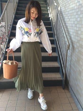 華やかな刺繍ブラウスには、ロング丈のプリーツスカートで軽やかに。バケツ型のバッグでトレンドも追加。足元をスニーカーにしてカジュアルさをプラスすると親しみやすいコーデになります。