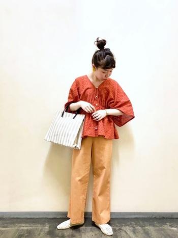 紅葉を思わせる鮮やかなオレンジの刺繍ブラウスも、着るだけで秋めくアイテム。濃さの違うオレンジのパンツを合わせてグラデーションに。バッグのストライプでアクセント付けも忘れずに。