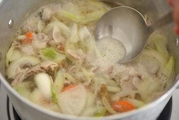 肉に火が通り、脂が具材全体に馴染んだら水またはだし汁を加えます。沸騰したらあくを取り、味噌の半量を先に入れます。