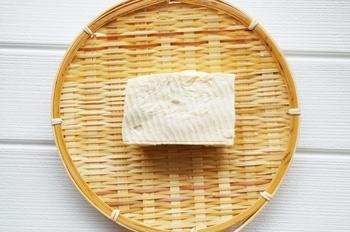 豆腐には90%ほど水分が含まれているので、豆腐ステーキやチャンプルーなどの炒め物や、白あえなどに使う場合は水切りをしてから調理をすると、味もよく染み込んで食感もよくなり、おいしく仕上がります。時間がある場合は重石を使う方法がしっかり水切りができておすすめですが、時間がない場合はレンジでも簡単にでき、重石を使う場合の3分の2ほど水分がとれます。