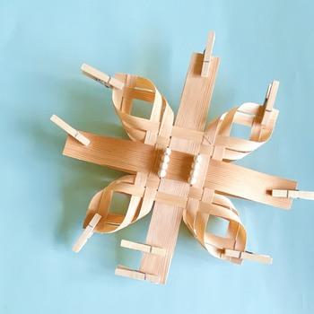ちなみにこのデザインでは、同じものを2つ制作→背中合わせに接着し、1つの立体的なオーナメントに仕上げます。  隅に付けた接着剤が乾いたら、十字に交差した太い経木を鉛筆の先のように鋭角にカットして、吊り下げひもをつければ完成です♪