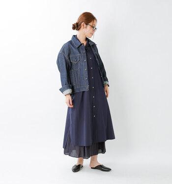 デニムジャケットに、同系色のシャツワンピースとスカートをレイヤードしたスタイリングです。全体を重ためのトーンで揃えているので、足首や手首を見せて抜け感をアピールするのがポイント。程よくナチュラルなコーディネートの完成です。