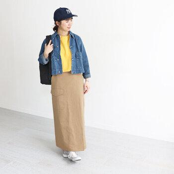 ショート丈のデニムジャケットに、青と相性のよいイエローのトップスを合わせたコーディネート。ベージュのタイトスカートにタックインして、大人のカジュアルスタイルにまとめています。スニーカーやキャップなど、小物もスポーティーなアイテムをチョイスして。