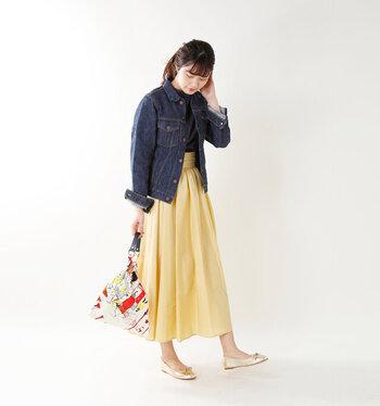 デニムジャケットに、イエローのフレアスカートを合わせたキレイめ×カジュアルのコーディネート。ダークトーンのトップスで上半身をキュッと引き締めて、ボトムスを暖色系で女性らしく仕上げています。ゴールドのパンプスとカラフルなバッグが、コーデのアクセントに♪