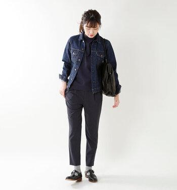 ネイビーのストライプパンツに、同系色の無地トップスを合わせたクールな組み合わせ。大人シックにまとめたスタイルに、デニムジャケットでカジュアルダウン。足元は黒シューズ×靴下でメンズライクな印象に。