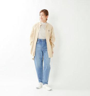 薄いブルーのデニムパンツに、白系のハイネックトップスをタックイン。上からベージュのシャツを羽織って、暖かみのあるカジュアルにまとめています。スニーカーも白で揃えて、ナチュラル×カジュアルのミックスコーデに。