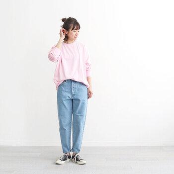 薄色デニムパンツに、ピンクのトップスをゆるくタックインしたスタイリングです。フロント部分を入れ込んで後ろに向かって下がるようなタックインは、体型カバーにもおすすめ。スニーカーでカジュアルにまとめていますが、トップスがピンクなので女性らしさもしっかりとアピールできます。