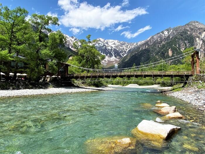 河童橋は、1891年に長野県松本市安曇上高地をとうとうと流れる梓川に架けられた全長37メートル、幅3.1メートルのカラマツ製の橋です。ここからは、日本で3番目の標高を誇る奥穂高岳を主峰としる穂高岳連邦を臨むことができ、山岳絶景スポットとして大勢の人々で賑わっています。
