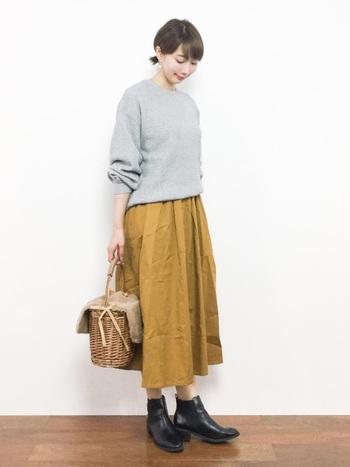 からし色スカートはグレーを合わせると秋らしい印象に。ナチュラルなカゴバックも素敵です。ブラックのブーツがコーデを引き締めてくれています。