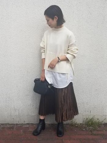 シルエットが綺麗なプリーツスカートに、異素材レイヤード!ニットを重ねてトレンドコーデに。小物はブラックで揃えてシンプルにして、コーデを引き立てて。