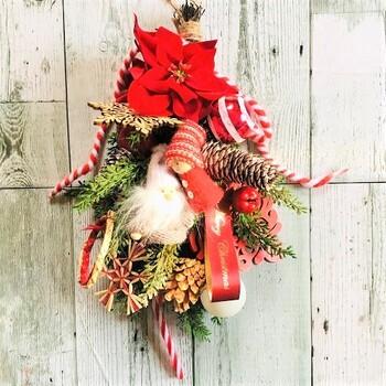 クリスマスレッドの松ぼっくりのスワッグ。松ぼっくりや木の実の間に、小人の人形やキャンディースティック、カラーボールなど異素材のものを入れています。ぽってり感じが温かい印象。クリスマスらしさいっぱいにまとめたいときに参考になりそうなデザインです。