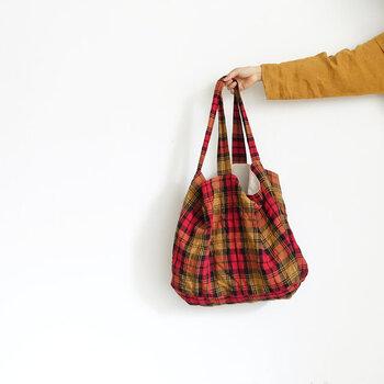 リネン素材の大きめトートバッグは、くったりとした素材感がナチュラルな印象を与えるアイテム。暖かみのあるタータンチェック柄で、季節を問わずに活用できます。