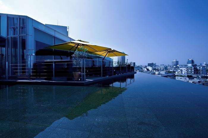 青山の新ランドマーク「AO(アオ)」の5階にある「TWO ROOMS GRILL|BAR(ツールームズグリルバー)」のテラス席は、まるで水辺に浮かんでいるかのようなインフィニティな雰囲気です。