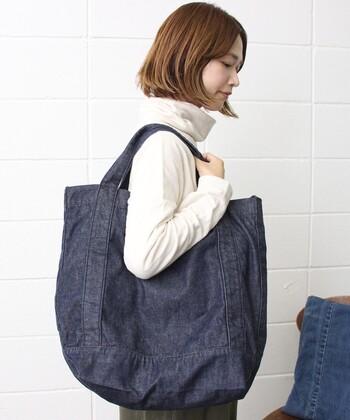 たっぷりと入るゆったりサイズのデニムトートバッグ。サイドにタックボタンが付属しているので、大きさを好みに合わせて調節できるのがポイントです。食料品など多めの買い物でも、しっかり対応できるサイズ感。カジュアルな着こなしが多い方には、デイリーに使えるトートバッグです。