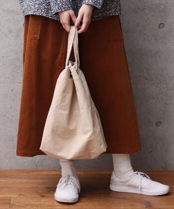ざっくりと使えるシンプルデザインのトートバッグですが、なんと持ち方のバリエーションは4種類。持ち手を両側のリングから引っ張れば、トートバッグとして使えます。ひもの出し方によって、巾着のような形に絞ることも可能。