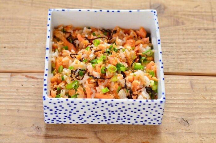 温かいご飯にほぐし鮭や塩昆布などを混ぜるだけの簡単混ぜご飯です。見た目華やかでお弁当にもおすすめ。小口ネギをまぶして彩り良く。