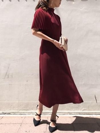 なかなか挑戦しづらい赤いドレスも、ボルドーなら着こなしやすいはず。クラシカルな立襟とケープのようにも見えるプリーツスリーブがエレガントで、上品にまとまります。ミモレ丈なら、足元のおしゃれも楽しめますね。