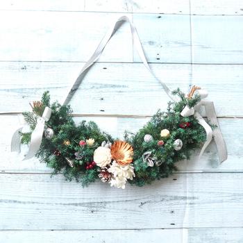 プリザーブドフラワーとドライフラワーを使ったハーフムーンスワッグ。ヒムロスギの濃い緑色がクリスマスらしさを演出してくれます。ハーフムーンは、一般的なスワッグとはまた違った優しい印象があり、人気ですね。