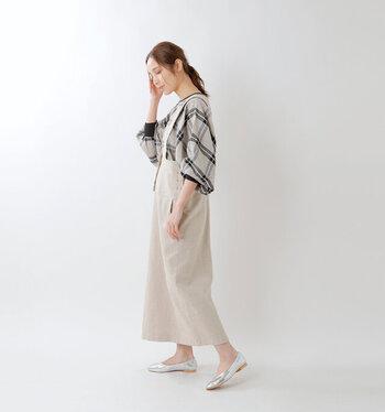 チェック柄のプルオ―バーを、ベージュのサロペットスカートに合わせたコーディネートです。同系色のアイテムを選んでいるので、統一感がありチェック柄も大人な印象に。足元はシルバーのパンプスでアクセントをプラス。