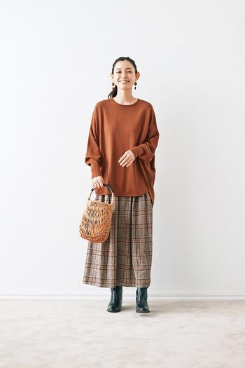 ブラウンのチェック柄スカートに、トーン違いのブラウントップスを合わせた同系色コーデ。足元は黒のブーツを合わせて、季節感をアピールしつつ暖色系コーデの引き締めポイントにも◎