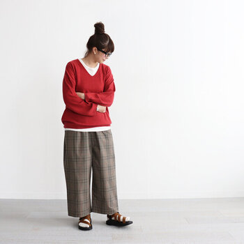 ブラウン系のチェック柄ワイドパンツに、赤のニットを合わせたスタイリングです。ブラウン×赤はこれからの季節にぴったりなカラーリング。白インナーをちらりと覗かせているのがポイント。足元は白靴下にサンダルを合わせて、抜け感をプラスしています。