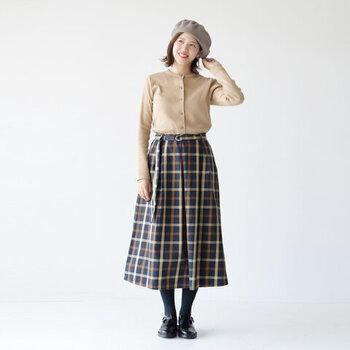 ネイビー系のチェック柄スカートに、ベージュのカーディガンを合わせたスタイリング。ボタンを全て留めてからきっちりとタックインして、トップス風の着こなしに仕上げています。ベレー帽やローファーを合わせて、ロンドンガール風のコーディネートに仕上げています。