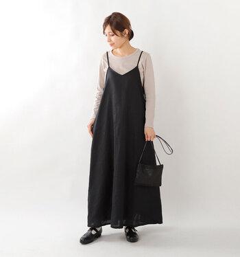 黒のキャミワンピースに、ベージュの無地トップスを合わせたシンプルなコーディネート。靴やバッグなど小物も黒で揃えて、全体的に統一感のある大人っぽいスタイリングにまとめています。