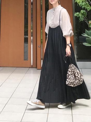 黒のキャミワンピースに、シアーブラウスを合わせたコーディネート。フェミニンな印象を与えるスタイリングですが、足元のベージュスニーカーで上手にカジュアルダウンしています。手に持ったレオパード柄のバッグで、ベーシックカラーの着こなしにほどよいワンアクセントをプラス。