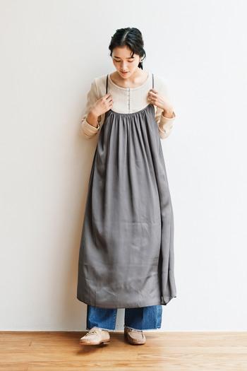 グレーのキャミワンピースに、薄いベージュの無地トップスを合わせたコーディネートです。そのままでもナチュラルな印象ですが、デニムのワイドパンツをレイヤードして裾から覗かせることで、トレンド感もしっかりおさえたスタイリングに。