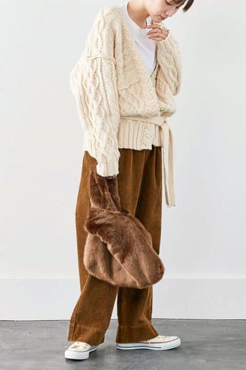コーデュロイ素材のワイドパンツに、ざっくりニットカーディガンを合わせたコーディネート。トップスはシンプルな白をチョイスして、暖かみのあるカラーリングにまとめています。ボア素材のトートバッグはパンツと色を合わせて、季節感たっぷりな着こなしに。