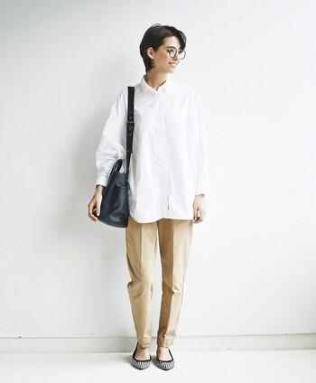 センタープレス入りのベージュパンツに、白のシャツを合わせたベーシックなスタイリング。オフィスカジュアルとしても活躍してくれる、シンプルな大人スタイルです。黒のショルダーバッグとモノトーンのパンプスを合わせて、落ち着いた雰囲気にまとめています。